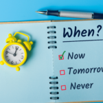 Retro alarm clock and a notebook with a the headline When? Putting Off Estate Planning