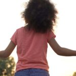 child holding the hands of adults - 3 ways a lawyer helps with fetility law can help