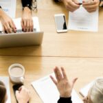 people around a table negotiating - 5 stages of mediation